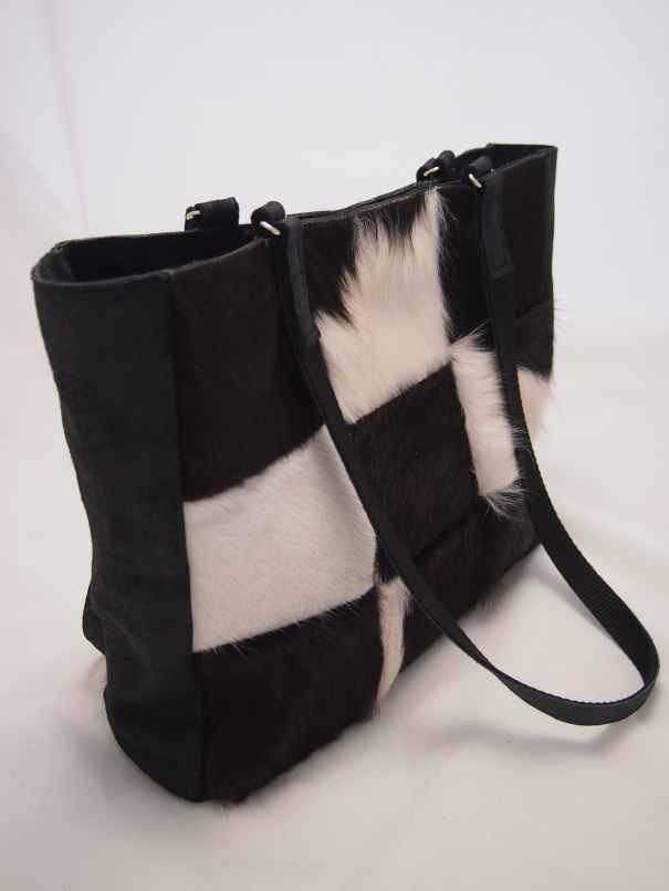Edith is een patchwork shopper gemaakt van zwart/witte koeienhuid en zwart leer.