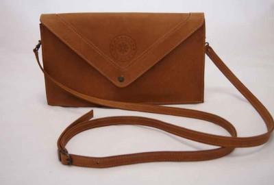 Lederen clutch 'Juliette' is uitgevoerd in bruin gevet leer en komt met een afneembare schouderband.